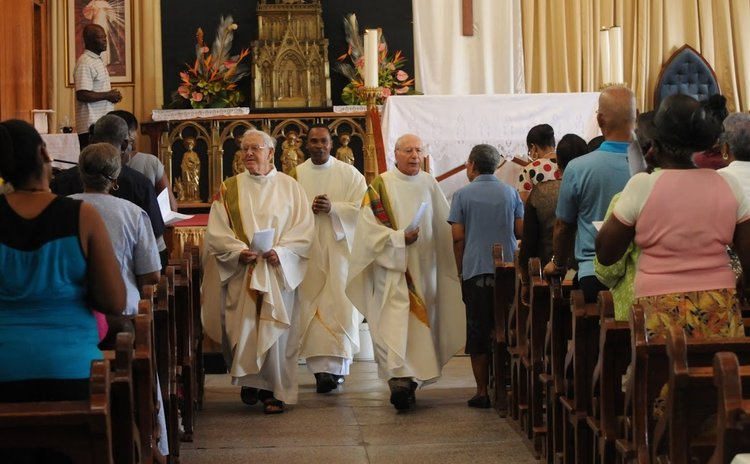Fr Charles,left, walks with two other priests at the Roseau Cathedral