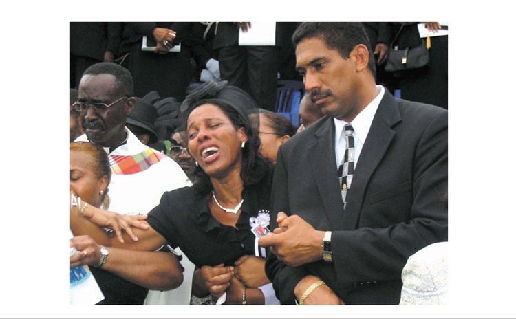Mrs Justina Charles cries at the funeral