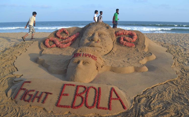 BHUBANESWAR, Aug. 20, 2014 (Xinhua) -- Visitors walk past a sand sculpture to fight against EBOLA virus created by Sudarshan Pattnaik at Puri beach, India, Aug. 19, 2014