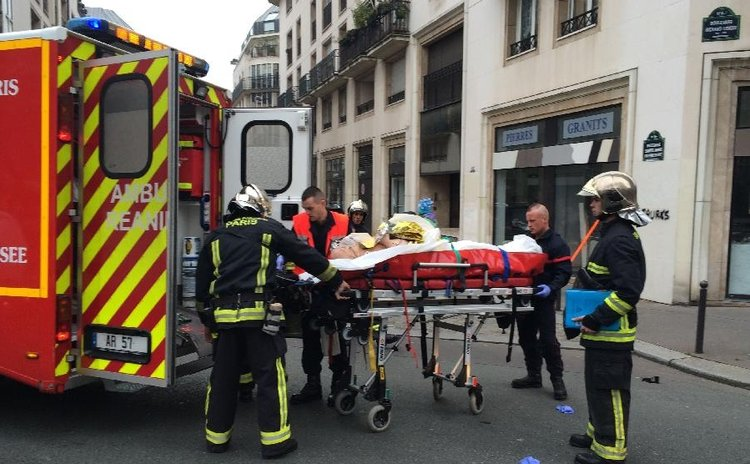 Firefighters carry an injured man on a stretcher in front of the offices of the French satirical newspaper Charlie Hebdo in Paris on January 7, 2015. (Xinhua/AFP Photo)