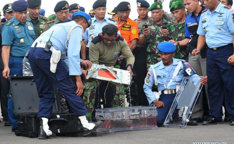 Indonesian military police carry the flight data recorder of the AirAsia Flight QZ8501 at Iskandar air base in Pangkalan Bun, Central Borneo, Indonesia, Jan. 12, 2015.