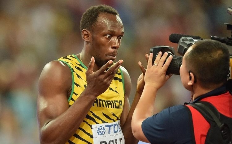 Bolt has fun with a cameraman after winning the 100 metres race