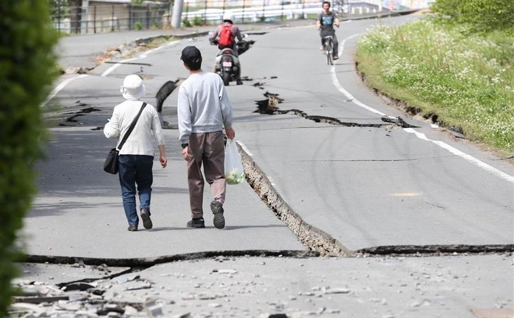 KUMAMOTO, April 16, 2016 (Xinhua) -- Residents walk on a street cracked by the earthquake in Mashiki, Kumamoto prefecture in southwestern Japan, April 16, 2016.
