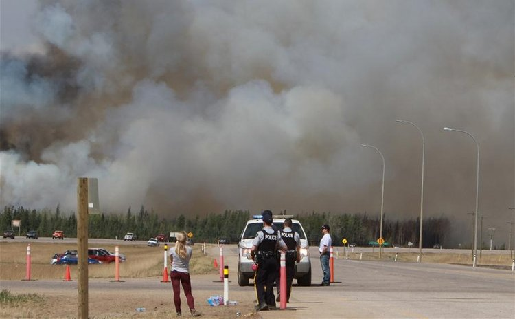 EDMONTON, May 8, 2016 (Xinhua) -- Policemen gather near the wildfire site in Alberta Province of Canada, May 7, 2016.  (Xinhua/Li Baodong)