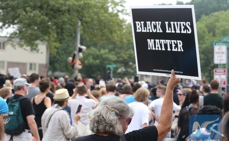 A woman holds up a BlackLives Matter sign at the Michael Brown memorial in Ferguson, Missouri, U.S., on August 9, 2015.