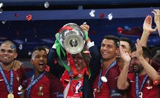 Fernando Santos(C), coach of Portugal celebrates with the trophy during the awarding ceremony after winning the Euro 2016 final football match against France in Paris, France, July 10, 2016.