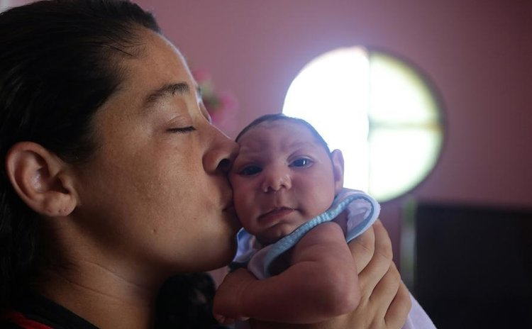 File photo taken on Feb. 4, 2016, shows Pollyana Rabello (L), holding her baby, Luiz Philipe, who was born with microcephaly, in their house in Marica, Rio de Janeiro state.