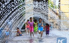 Children cool off in a wading pool in Toronto, Canada, June 20, 2016. Toronto issued an extreme heat alert on Monday, and the forecasted high was 34 degrees Celsius. (Xinhua/Zou Zheng)
