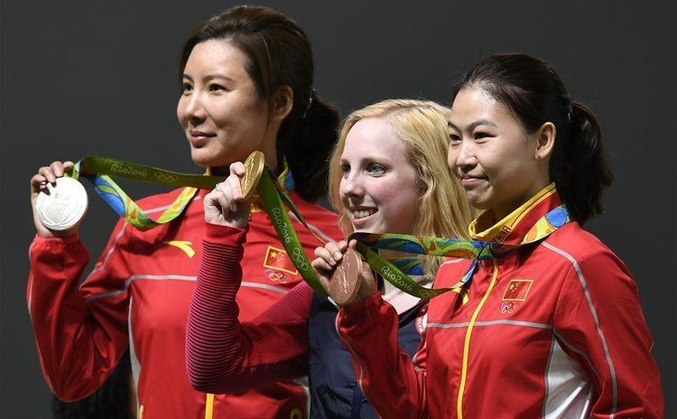 Virginia Thrasher (C) of the United States, Du Li (L) and Yi Siling of China attend the awarding ceremony of the Women's 10m Air Rifle of shooting of the 2016 Rio Olympic Games