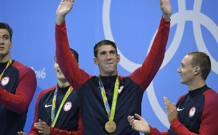 Michael Phelps (2nd, R) from the United States of America waves to the audience during the awarding ceremony for the men's 4x100m freestyle relay at the 2016 Rio Olympic Games in Rio de Janeiro