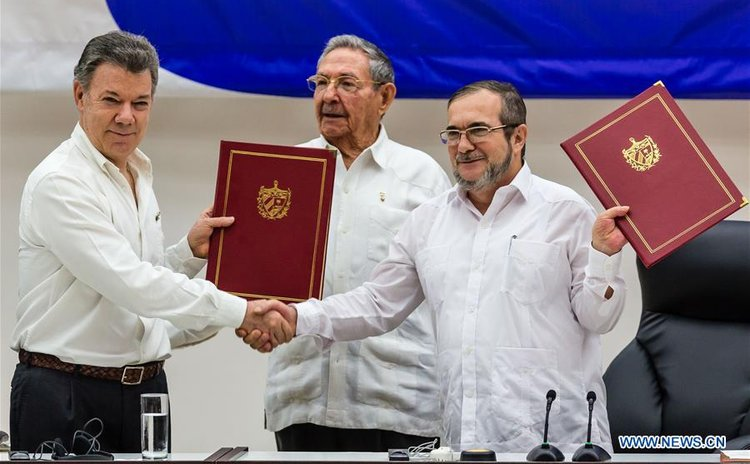 Colombian President Juan Manuel Santos (L) and Timoleon Jimenez (R), the top leader of the Revolutionary Armed Forces of Colombia (FARC), exchange pacts while Cuban President Raul Castro witnesses
