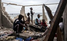 Image provided by the United Nations Children's Fund (UNICEF) shows people sitting on a structure devastated by Hurricane Matthew, in the neighborhood of La Savane, Les Cayes, Haiti, on Oct. 9, 2016