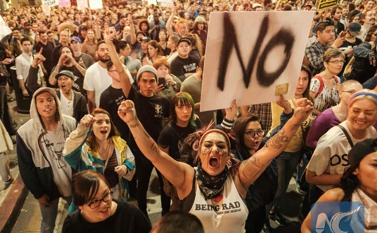 Demonstrators gather to protest a day after President-elect Donald Trump's victory, at a rally outside Los Angeles City Hall in Los Angeles, California, on November 9, 2016. (AFP/Xinhua)