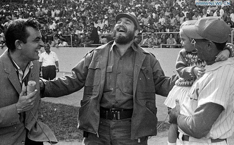 Undated file photo shows Fidel Castro (C) interacting with a journalist and a baseball player in Latinoamericano Stadium in Havana, Cuba