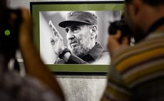 File photo taken on Aug. 12, 2014 shows people taking photos of a picture of Fidel Castro prior to his 88th birthday in Havana, Cuba