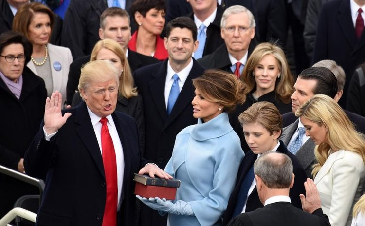 U.S. President Donald Trump(L) takes the oath of office during the presidential inauguration ceremony at the U.S. Capitol in Washington D.C., the United States, on Jan. 20, 2017