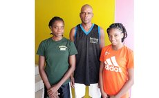 Curtis John with his basketball daughters, Curnia (L), and Vanelcia