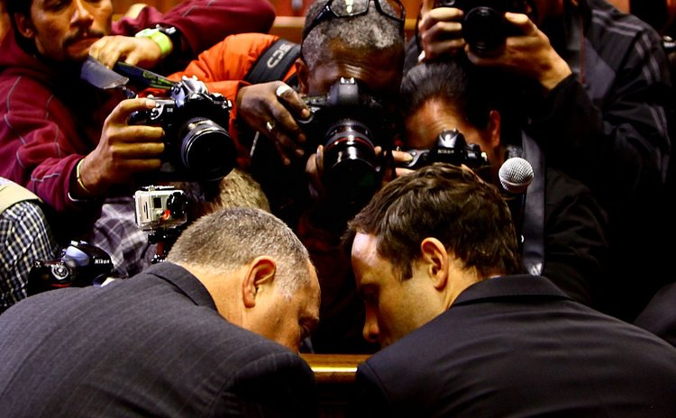 PRETORIA, Paralympic running star Oscar Pistorius (R) reacts inside the magistrates court in Pretoria, South Africa.