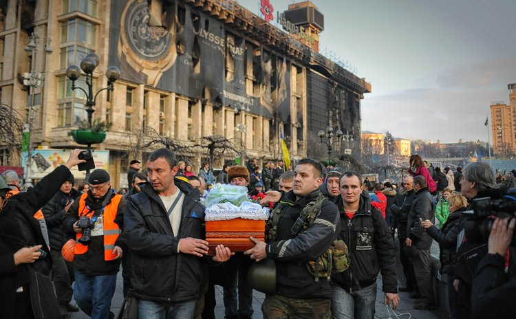 Protesters carry a coffin in the capital