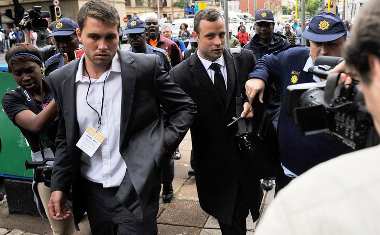 PRETORIA, March 5, 2014 (Xinhua) – S. African Paralympic athlete Oscar Pistorius (C) is escorted outside court during a recess on the third day of his trial at the high court in Pretoria, S. Africa.