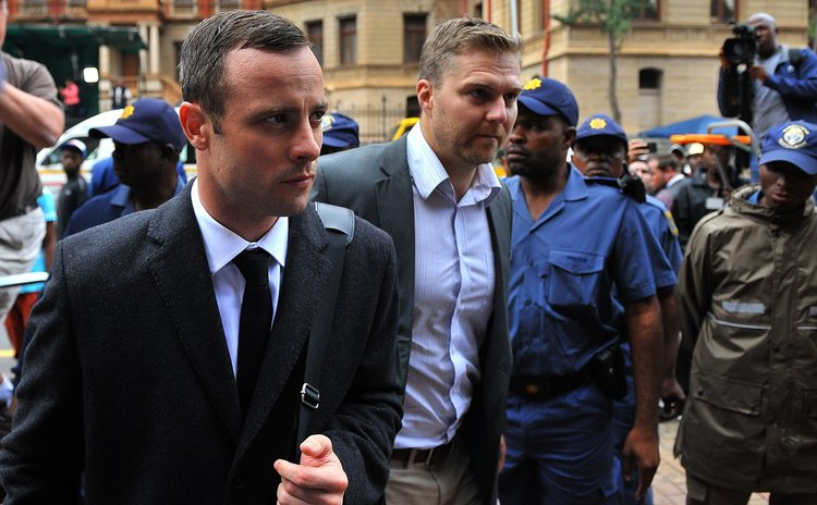 PRETORIA, March 10, 2014 (Xinhua) -- Oscar Pistorius (L) walks to Pretoria's North Gauteng High Court  in Pretoria, South Africa, on March 10, 2014, at the start of the second week Oscar Pistorius' mu