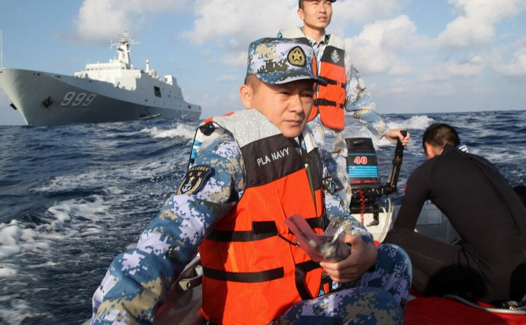 March 14, 2014 (Xinhua) -- Rescuers aboard the Chinese naval vessel Jianggangshan take a boat to possible crash site of missing Malaysia Airlines flight MH370, March 13, 2014
