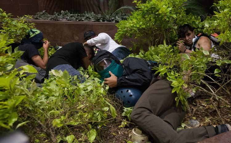 CARACAS, April 5, 2014 (Xinhua) -- Demonstrators take cover during a clash with Bolivarian National Guard in an anti-government protest, in Caracas, Venezuela, on April 4, 2014.