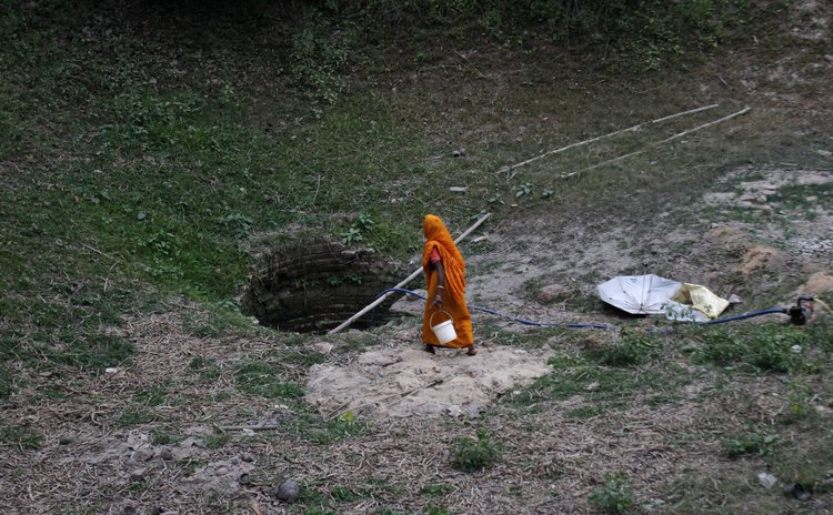 BHUBANESWAR, April 22, 2014 (Xinhua) -- A village woman reaches a well to collect water on the eve of World Earth Day.
