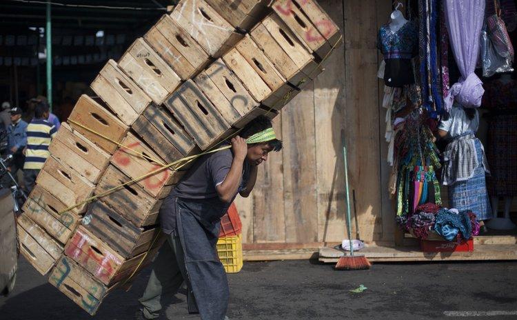 "GUATEMALA CITY, May 2, 2014 (Xinhua) -- A man carries boxes at ""La Terminal"" market in Guatemala City, capital of Guatemala, on May 1, 2014, the International Labor Day."