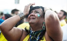 A Brazil's fan reacts while watching a semi-final match between Brazil and Germany of 2014 FIFA World Cup