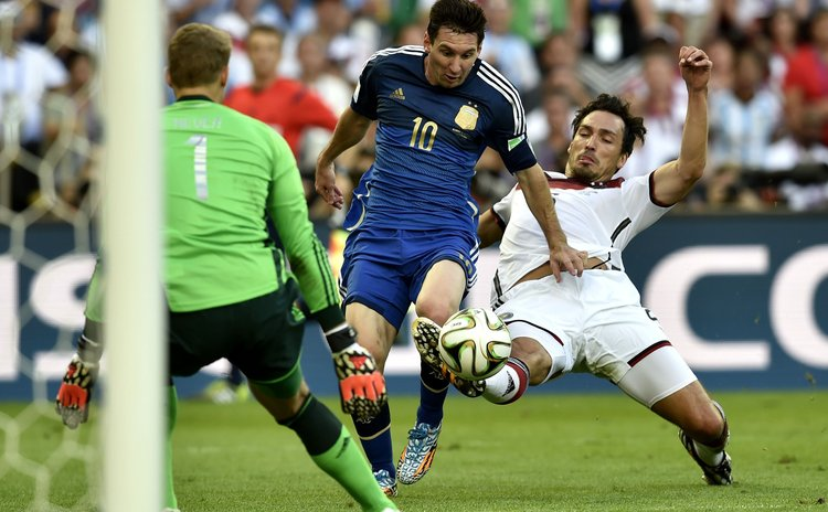 Germany's Mats Hummels (R) and goalkeeper Manuel Neuer (L) defend against Argentina's Lionel Messi during the final match between Germany and Argentina of 2014 FIFA World Cup at the Estadio do Maraca