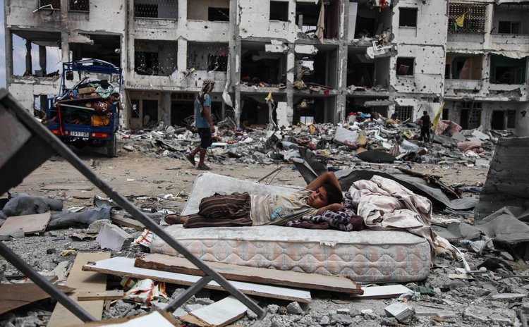 GAZA STRIP, Aug. 4, 2014 (Xinhua) -- A Palestinian boy rests on a mattress as he collects belongings from his destroyed house in the northern Gaza Strip town of Beit Lahiya, on Aug. 4, 2014