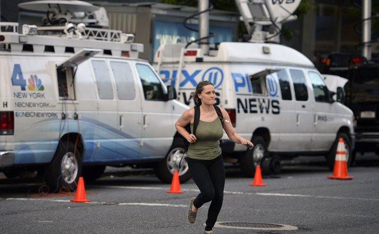 NEW YORK, Aug. 5, 2014 (Xinhua) -- A woman walks past brocasting vans in front of Mount Sinai Hospital in New York, the United States, Aug. 4, 2014