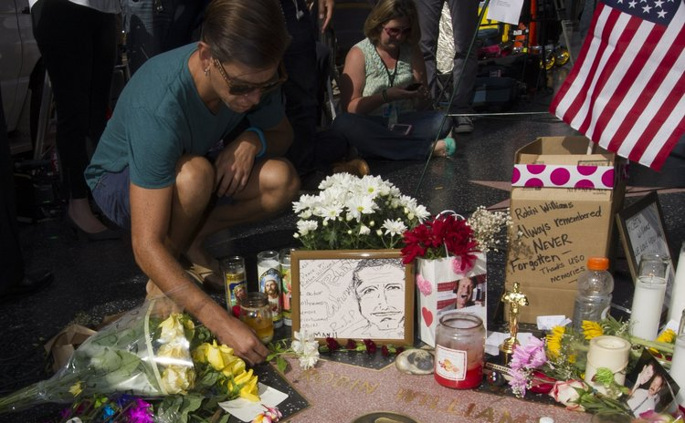 LOS ANGELES, Aug. 12, 2014 (Xinhua) -- A man lays flowers at Robin Williams' star on the Hollywood Walk of Fame in Hollywood, California, the United States, Aug. 12, 2014.
