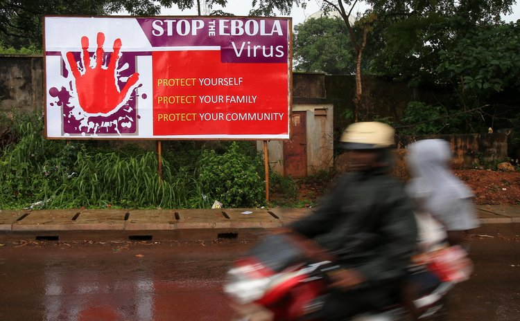 FREETOWN, Aug. 18, 2014 (Xinhua) -- People ride past a board with control and prevention information of the Ebola epidemic outbreak in the Ebola-affected Freetown, capital of Sierra Leone, Aug. 17, 20