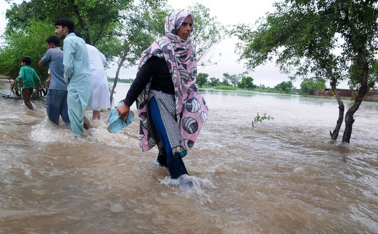 GUJRANWALA, Sept. 7, 2014 (Xinhua) -- Pakistani people wade through flooded water in eastern Pakistan's Gujranwala on Sept. 6, 2014