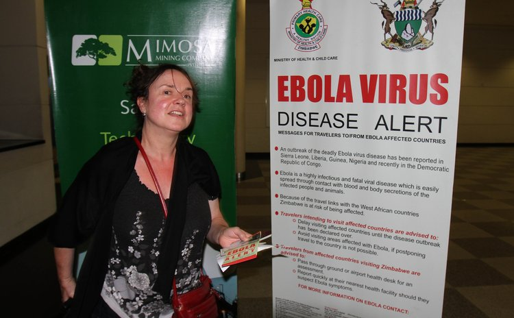 HARARE, Oct. 6, 2014 (Xinhua) -- A passenger holds a pamphlet on ebola prevention as she arrives at Harare International Airport, Zimbabwe, Oct. 6, 2014