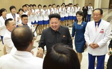 PYONGYANG, Oct. 19, 2014 (Xinhua) -- Korean Central News Agency (KCNA) photo shows Kim Jong Un, and wife Ri Sol-Ju (2nd R) meeting with gold medalists of the 17th Asian Games
