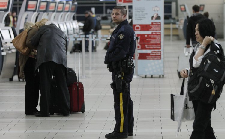 VANCOUVER, Oct. 23, 2014 (Xinhua) -- A policeman patrols at departure hall of Vancouver International Airport in Vancouver, Canada, Oct. 22, 2014.