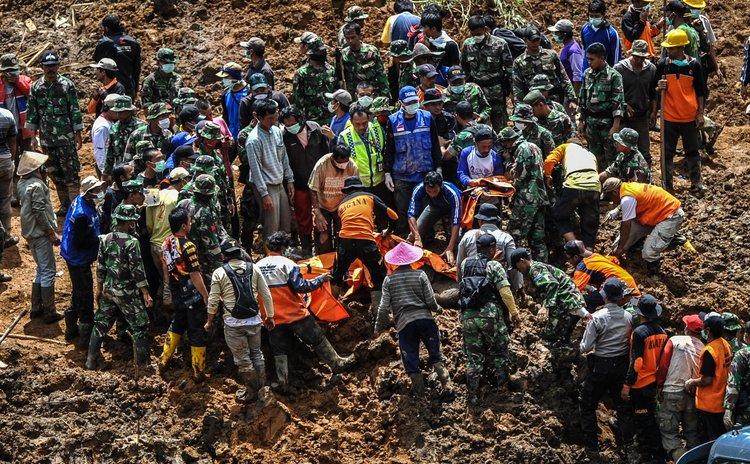 BANJARNEGARA, Dec. 15, 2014 (Xinhua) -- Soldiers recover a dead body as an escavator dredges mud hoarding a road at Sampang village in Banjarnegara, Indonesia, Dec. 15, 2014.