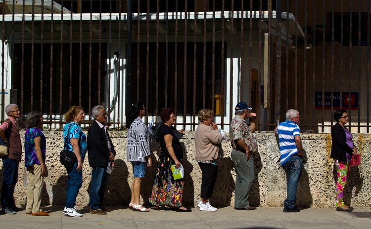 HAVANA, Dec. 17, 2014 (Xinhua) -- Cubans stand in queue to deal with consul business outside the main building of United States Interests Section in Havana, capital of Cuba, Dec. 17, 2014.