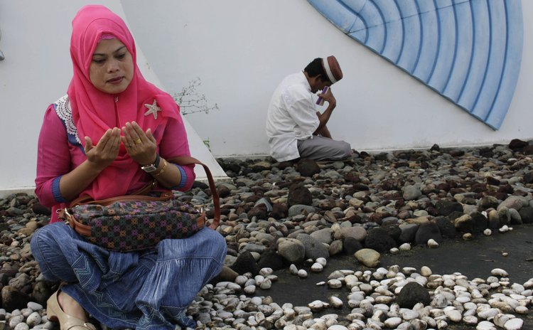 BANDA ACEH, Dec. 26, 2014 (Xinhua) -- Indonesian Muslims pray during the commemoration of 10th anniversary of the devastating tsunami at Sirion mass grave in Banda Aceh, Indonesia, Dec. 26, 2014