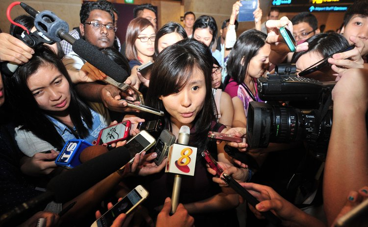 SINGAPORE, Dec. 28, 2014 (Xinhua) -- A fiancee (C) of a passenger on AirAsia flight QZ8501 speaks to the media at Singapore's Changi Airport, on Dec. 28, 2014.