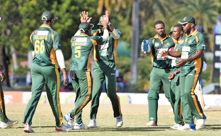 Alick Athanaze is congratulated by teammates after taking his first wicket