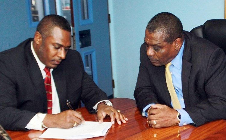 BELLO's Managing Director Michael Fagan and AID Bank's Manager Julius Corbet sign agreement