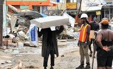 On Hillsborough Street, Roseau, a man carries a mattress and a pillow along with it