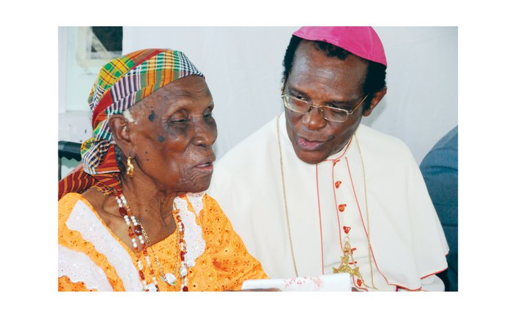 Archbishop Felix speaks with a centenarian in Soufriere in 2011