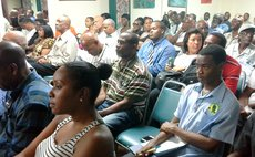 Persons listen to speakers at discussion on good governance