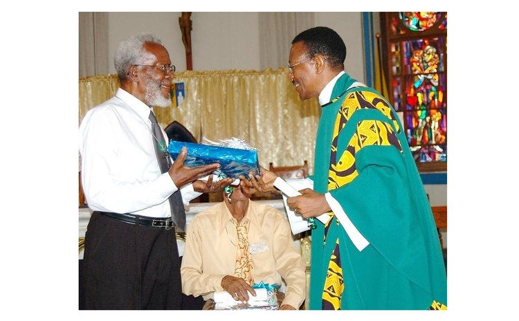 Bro Mo, left, receives gift from Fr. John Lewis