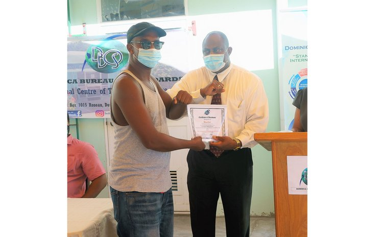 Trade Minister Ian Douglas hands certificate to course participant